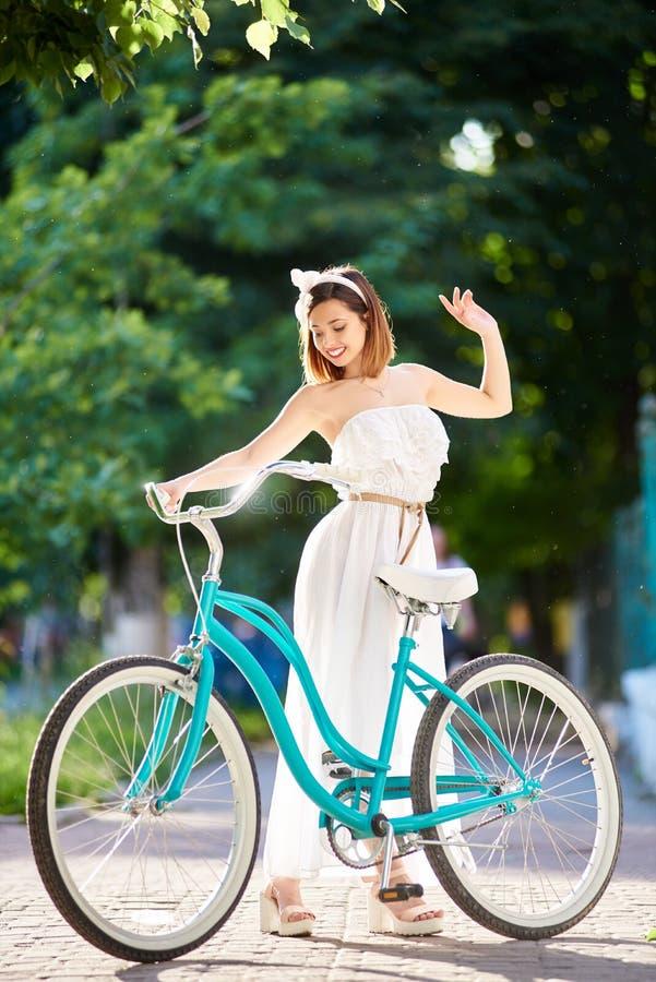Bicicleta retro azul perto da menina bonita na luz solar do verão fotos de stock royalty free