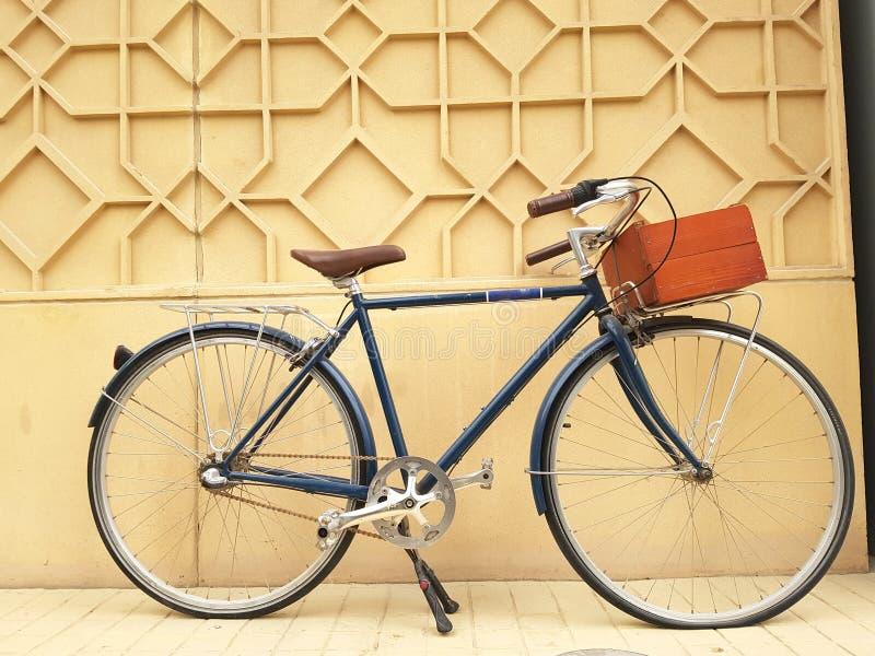 Bicicleta retro bonita ajustada contra uma parede e equipada com uma caixa de madeira para levar o material fotografia de stock