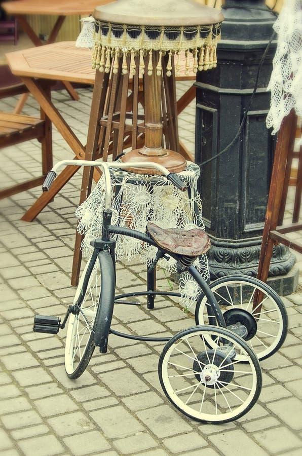 A bicicleta retro das crianças idosas da antiguidade dos objetos e a lâmpada de assoalho foto de stock