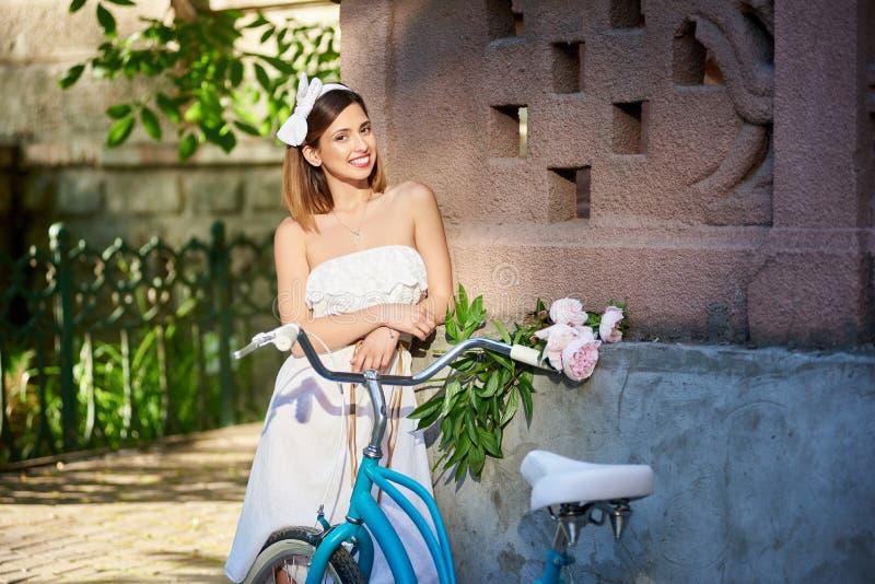 Bicicleta retro, peônias do ramalhete, menina romântica no fundo da parede imagem de stock royalty free