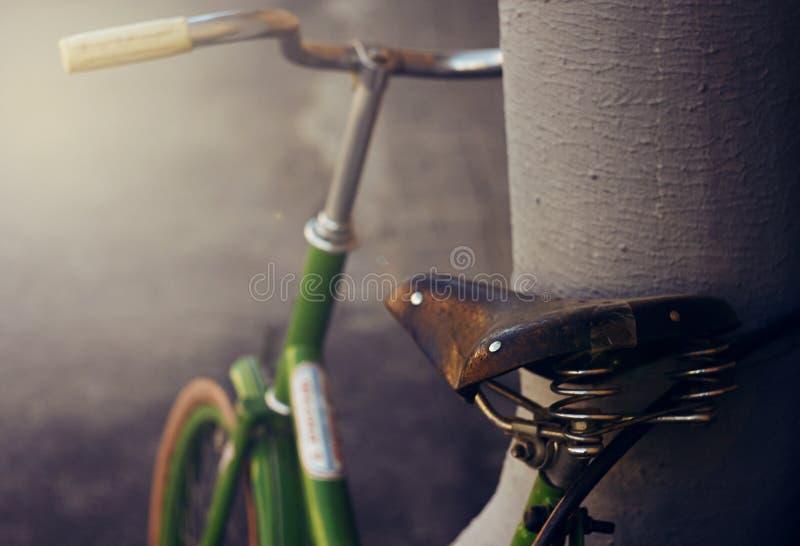 Bicicleta retro verde prendida ao cabo contra-roubo fotografia de stock
