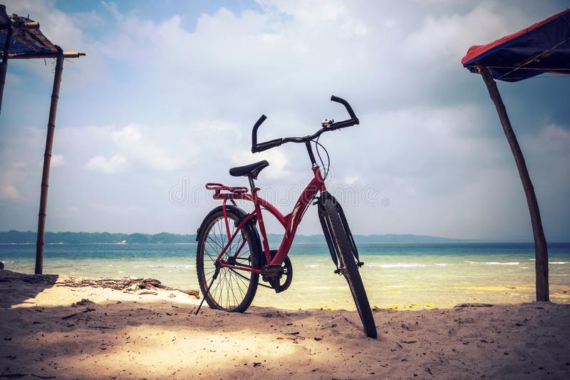 Bicicleta roja parqueada en la playa Estacionamiento de la bicicleta en la arena de la playa imágenes de archivo libres de regalías