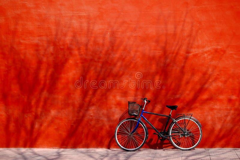 Bicicleta sob a parede vermelha fotografia de stock royalty free