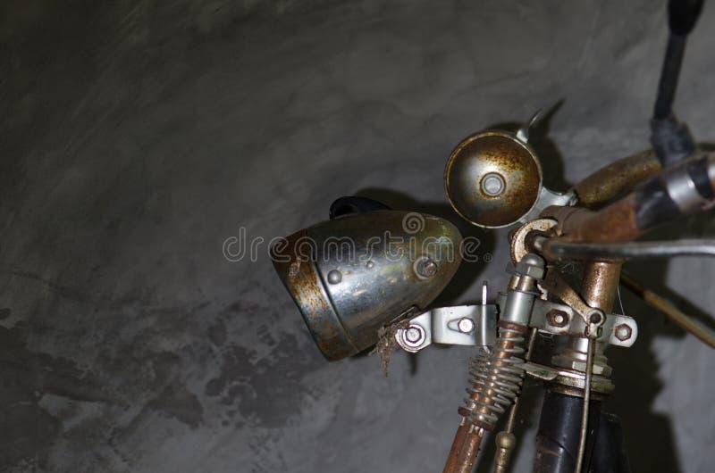 A bicicleta velha era parede estacionada do cimento deixada em casa Lâmpada velha oxidada foto de stock