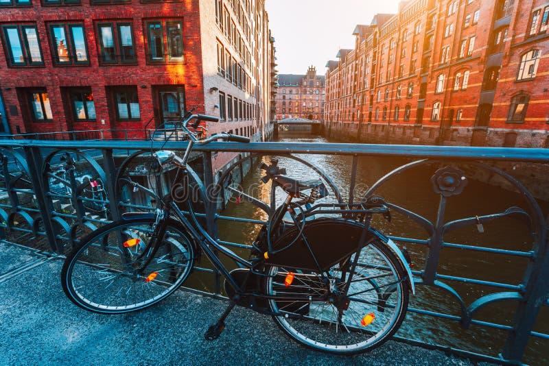 A bicicleta velha estacionou contra trilhos da mão de ferro na ponte no distrito do armazém de Hamburgo imagens de stock