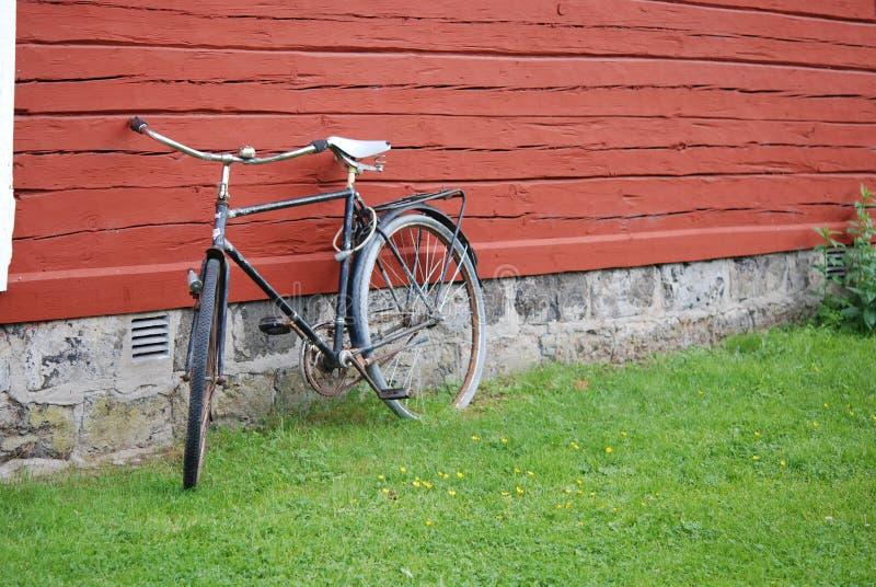 Bicicleta velha que inclina-se contra a parede vermelha fotos de stock