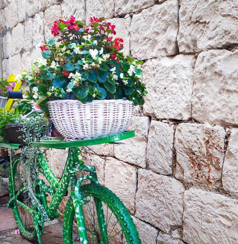 Bicicleta verde con una cesta de flores, decoración de otoño o verano imagen de archivo
