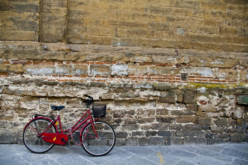 Bicicleta vermelha contra a parede de tijolo imagem de stock