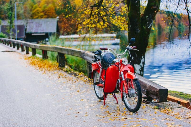 Bicicleta vermelha do motor do 'trotinette' do vintage perto do lago Bohinj, Eslovênia Cena outonal colorida imagem de stock