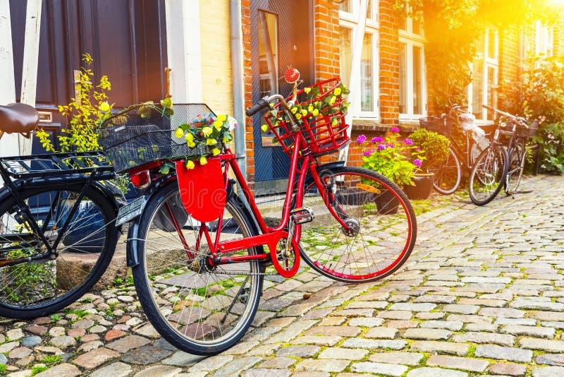 Bicicleta vermelha do vintage retro na rua de pedrinha na cidade velha imagem de stock royalty free