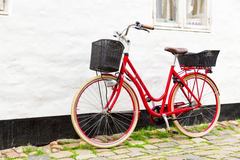 Bicicleta vermelha do vintage retro na rua de pedrinha na cidade velha imagem de stock
