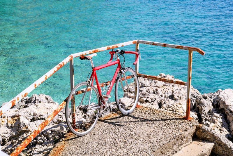 Bicicleta vermelha que inclina-se em uma cerca do ferro na praia pelo mar Bike a inclinação em trilhos no cais que enfrenta o hor imagem de stock