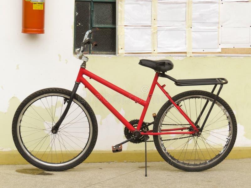 Bicicleta vermelha velha e gasta, abandonada que inclina-se contra a parede imagem de stock