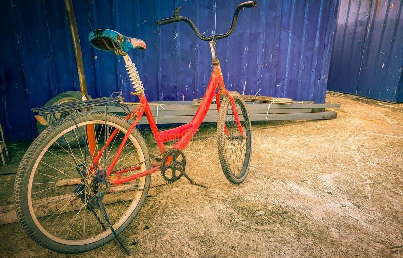 A bicicleta vermelha velha estacionou perto da parede azul fotografia de stock