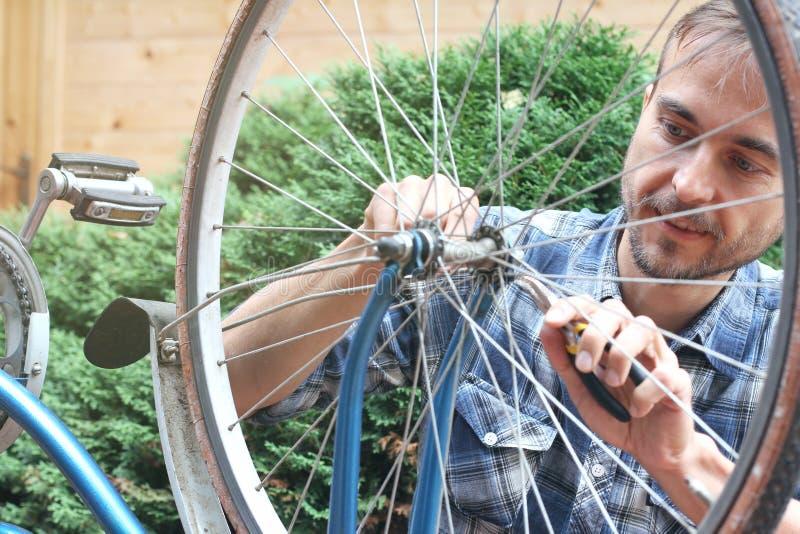 Bicicleta vieja del vintage de la reparación barbuda joven del hombre al aire libre imagen de archivo libre de regalías