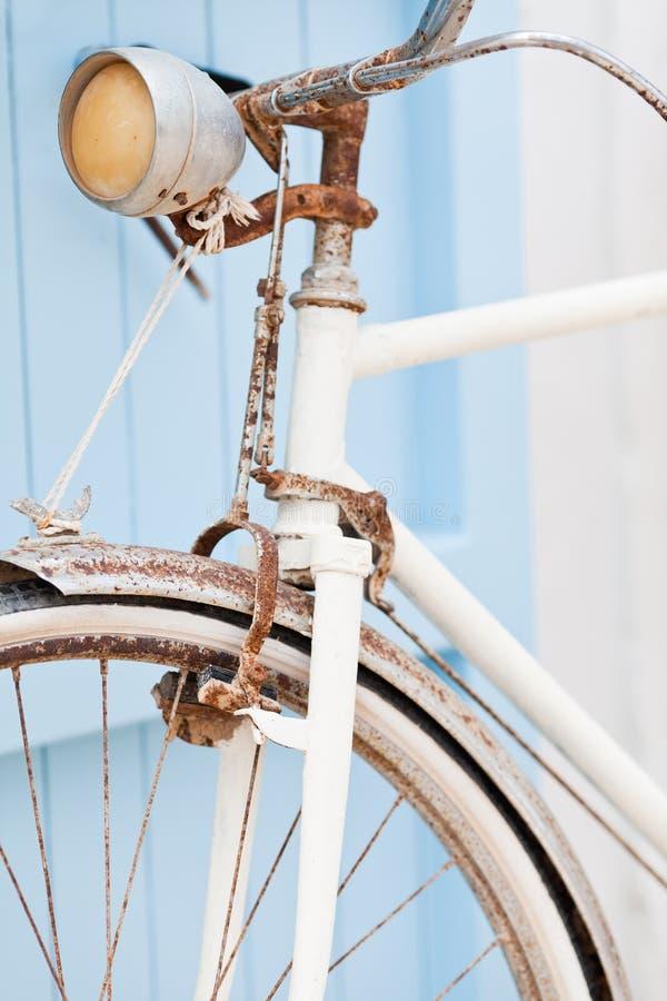 Bicicleta vieja que se inclina contra puerta azul. imagen de archivo libre de regalías