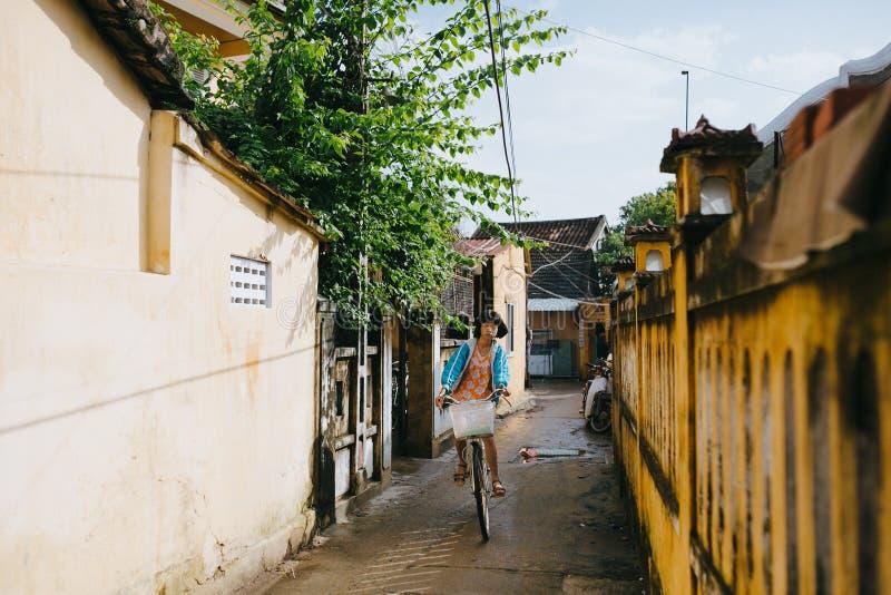 bicicleta vietnamita del montar a caballo de la muchacha en la calle estrecha en Hoi An, Vietnam fotos de archivo libres de regalías