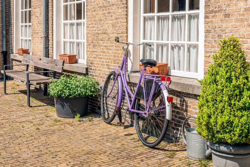 Bicicleta violeta das senhoras contra uma parede de tijolo imagens de stock royalty free