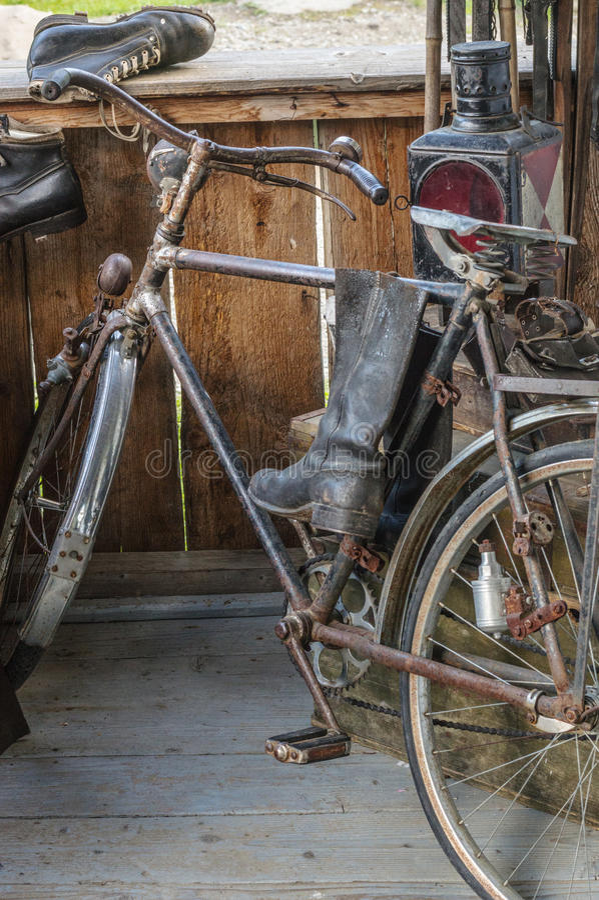 Bicicleta y botas viejas en el pórtico fotos de archivo libres de regalías