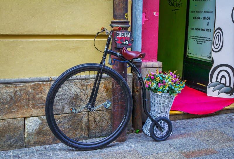 Bicicleta y cesta retras del estilo con las flores artificiales coloridas foto de archivo libre de regalías