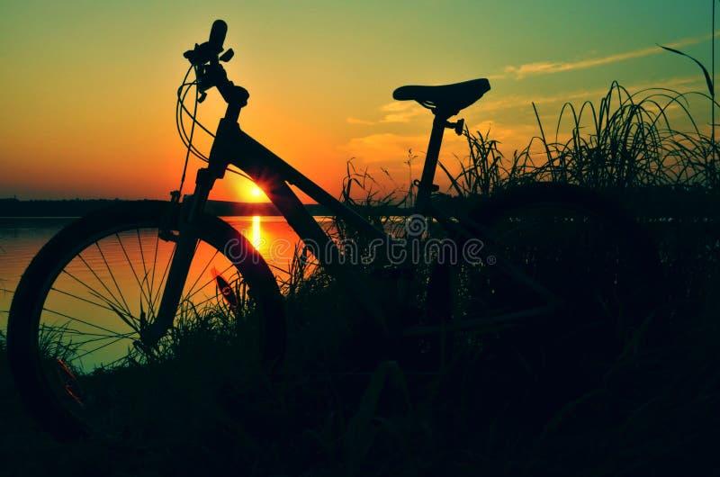 Bicicleta y puesta del sol imagen de archivo