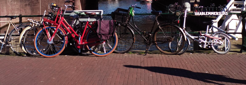 Bicicletas coloreadas que descansan sobre la verja de un puente sobre un canal de Amsterdam en una tarde imágenes de archivo libres de regalías