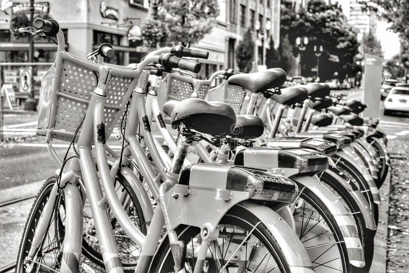 Bicicletas de alquiler en una calle urbana ocupada imagen de archivo libre de regalías