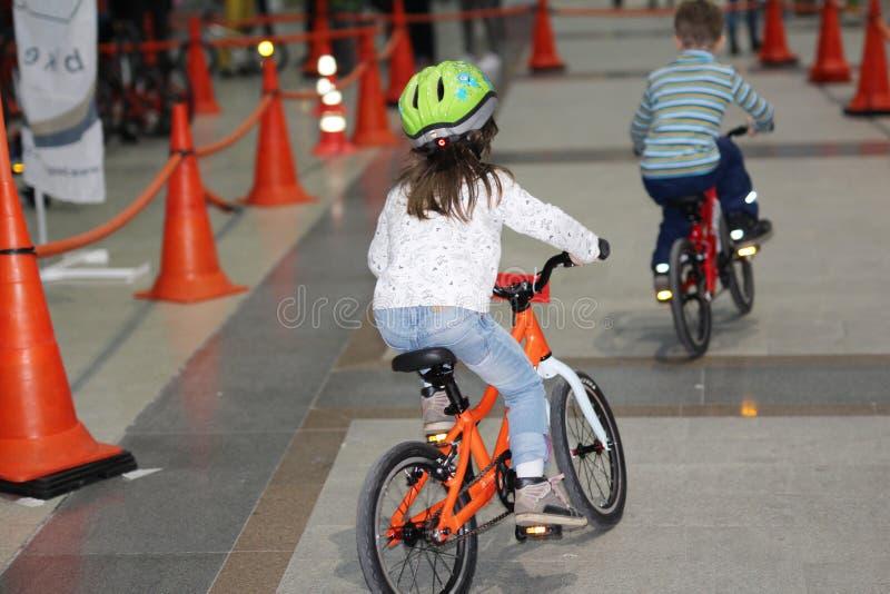 Bicicletas del paseo de un niño pequeño y de la muchacha en un camino especial imagenes de archivo