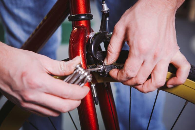 Bicicletas do reparo do tema Close-up de um uso caucasiano da mão do ` s do homem um grupo do hexágono da ferramenta ajustar e in fotografia de stock