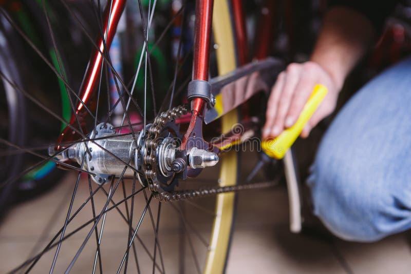 Bicicletas do reparo do tema Close-up de um uso caucasiano da mão do ` s do homem um lubrificante Chain em um lubrificador amarel imagem de stock