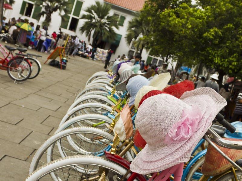 Bicicletas e chapéus coloridos para o aluguer fotografia de stock