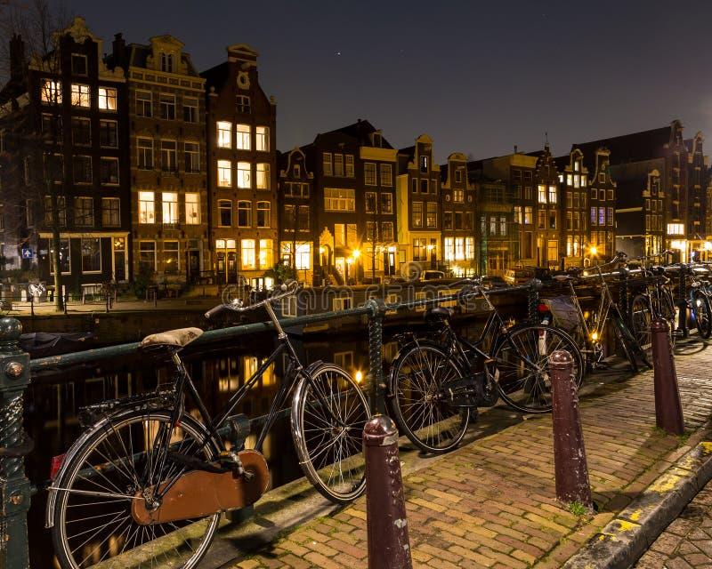 Bicicletas e construções ao longo dos canais de Amsterdão imagens de stock