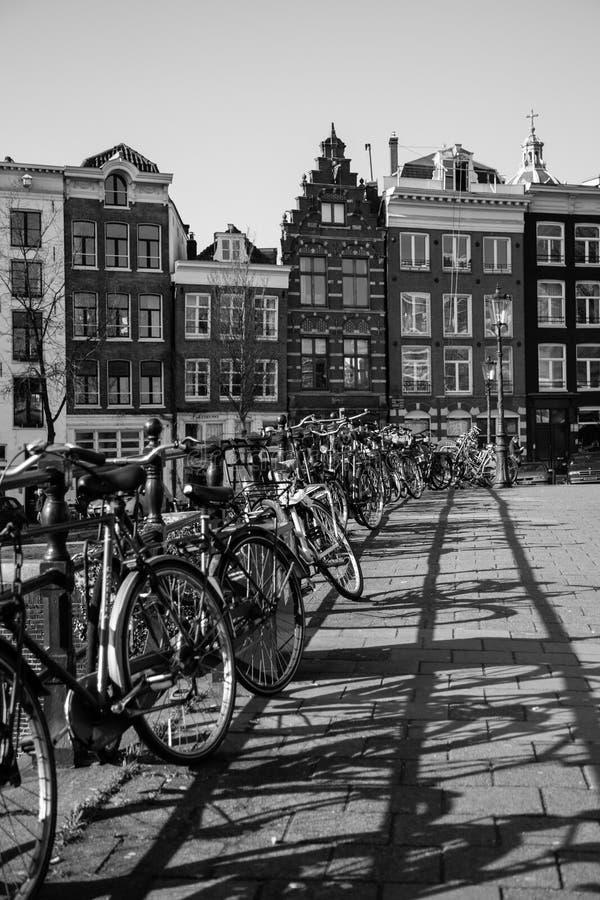 Bicicletas e construções em Amsterdão em preto e branco fotos de stock