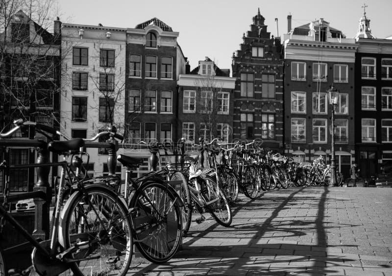 Bicicletas e construções em Amsterdão em preto e branco imagens de stock