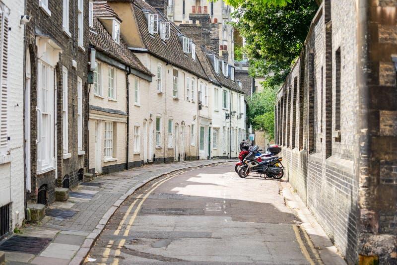 Bicicletas e Scooters estão estacionados fora de casas aterradas ao longo da rua estreita, Cambridge, Inglaterra, Reino Unido imagens de stock royalty free