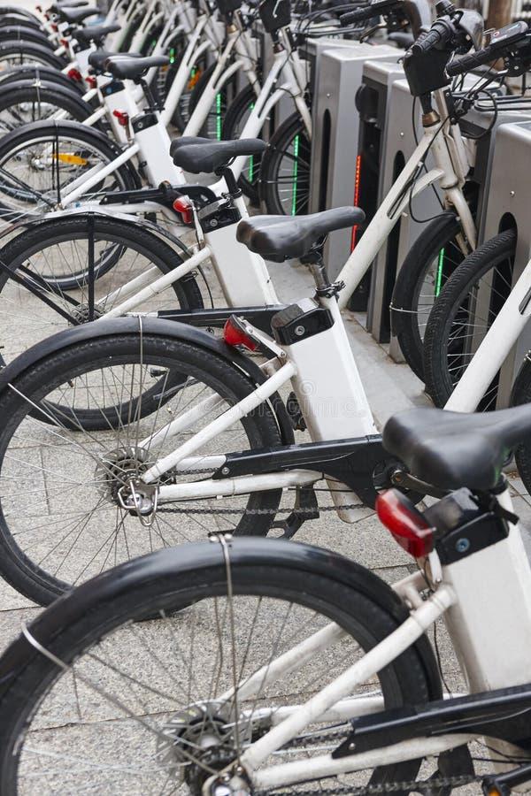 Bicicletas elétricas de carregamento na cidade Transporte verde urbano imagem de stock