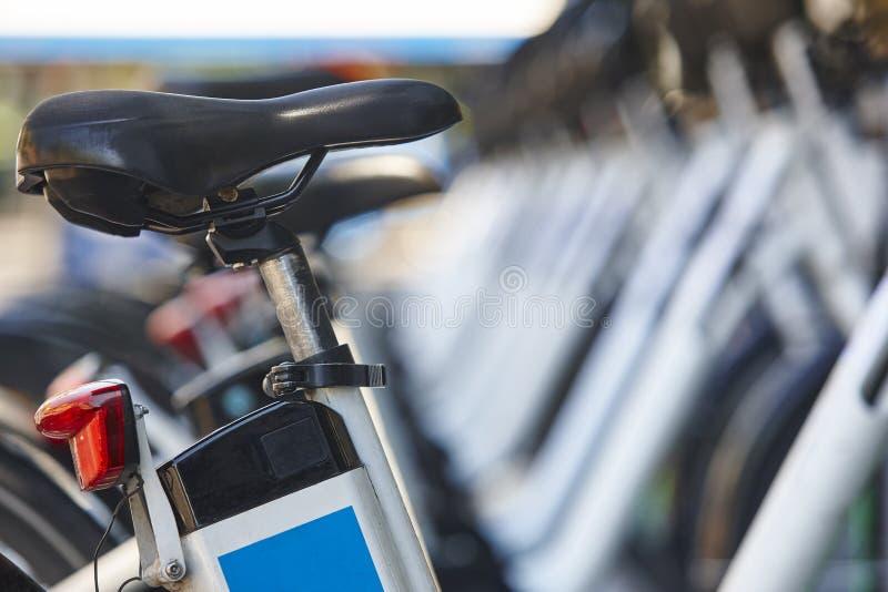 Bicicletas elétricas em um estacionamento Baterias de carregamento Ene renovável fotografia de stock royalty free