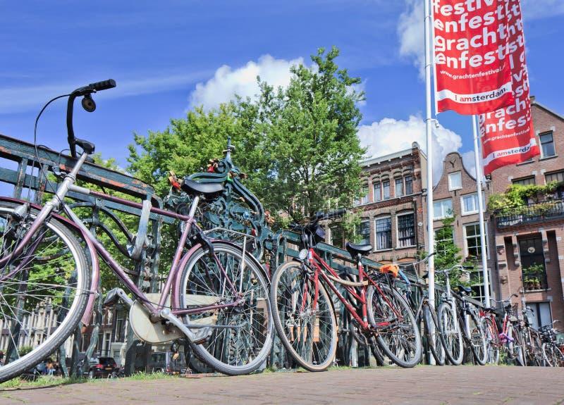 Bicicletas estacionadas contra trilhos na ponte, Amsterdão, Países Baixos fotografia de stock royalty free