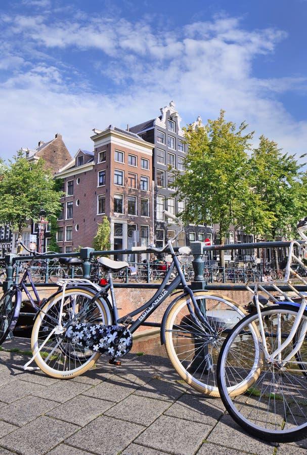 Bicicletas estacionadas contra trilhos na ponte, Amsterdão, Países Baixos imagens de stock royalty free