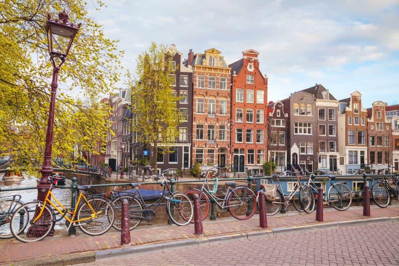 Bicicletas estacionadas em uma ponte em Amsterdão imagens de stock royalty free