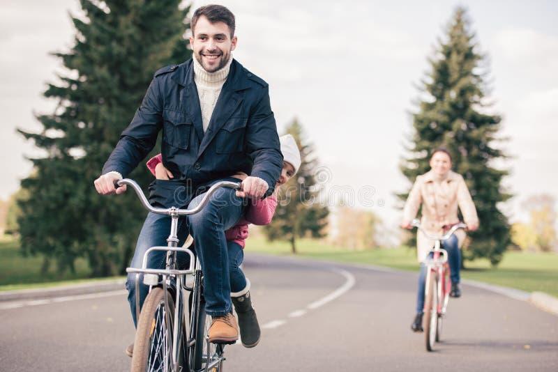 Bicicletas felizes da equitação da família no parque foto de stock