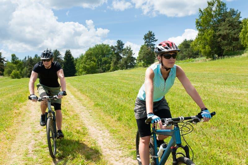 Bicicletas felizes da equitação dos pares do esporte no campo fotografia de stock royalty free