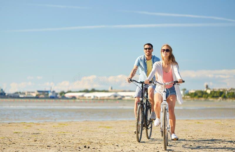 Bicicletas jovenes felices del montar a caballo de los pares en la playa fotos de archivo
