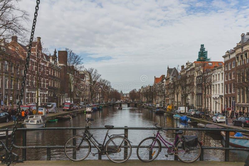 Bicicletas na ponte com vista do canal e das construções de Amsterdão do centro fotos de stock