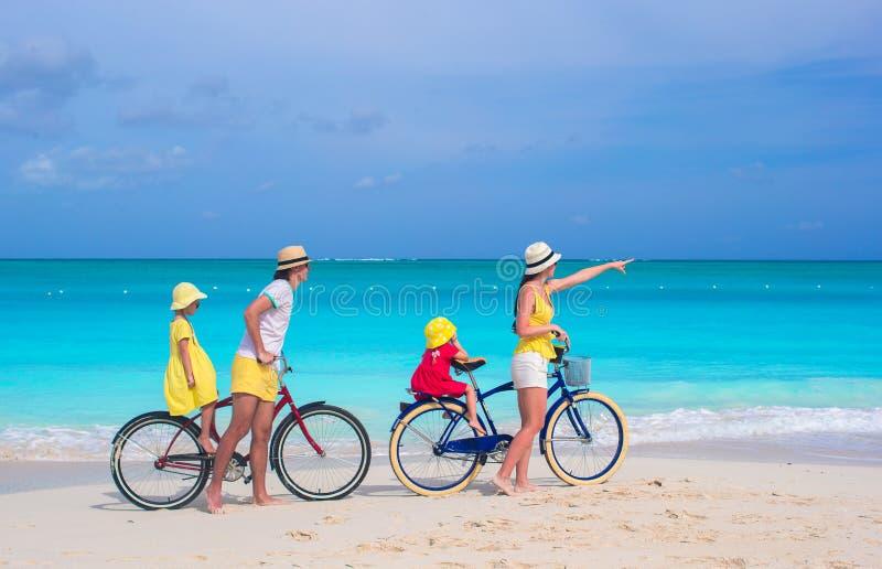Bicicletas novas da equitação da família na praia tropical fotos de stock royalty free