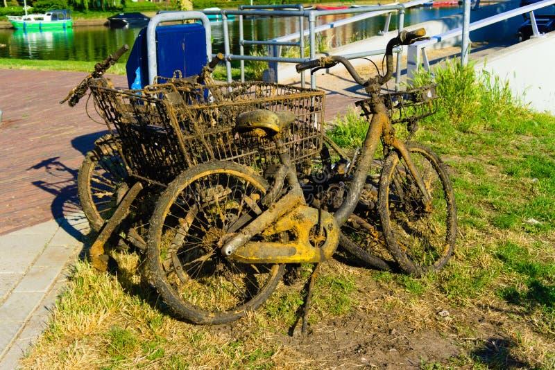Bicicletas pescadas fora do canal por líquidos de limpeza da cidade imagens de stock