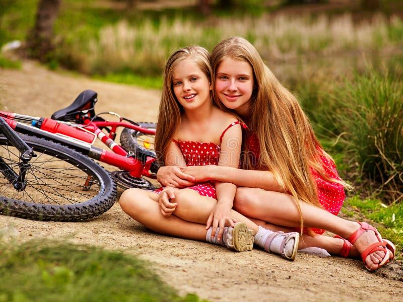 Bicicletas que dão um ciclo as crianças que sentam a estrada perto das bicicletas imagem de stock royalty free