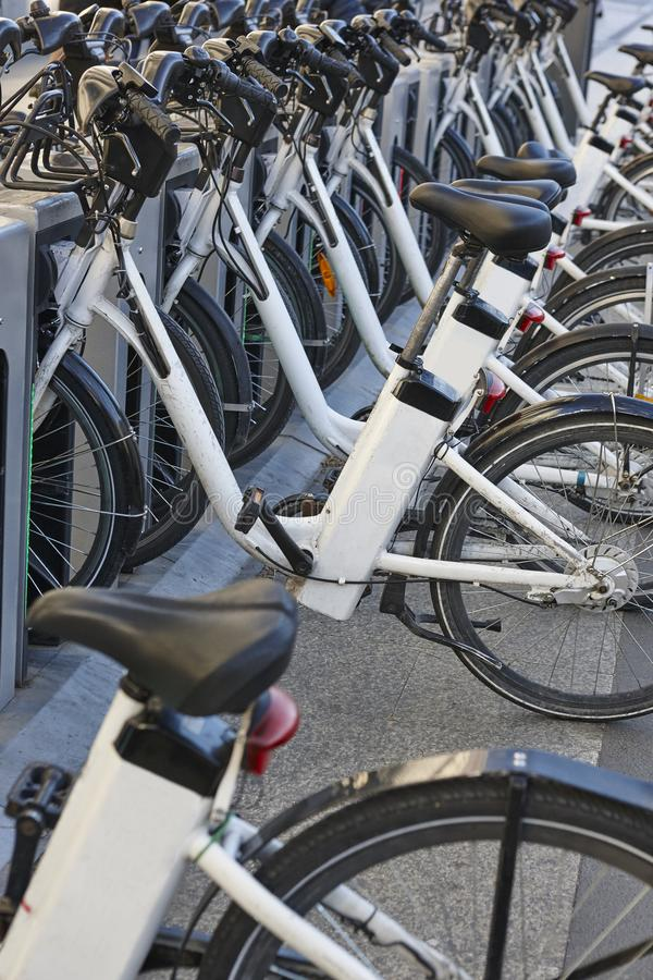 Bicicletas urbanas de carregamento da bateria elétrica na cidade Mobilidade sustentável imagens de stock