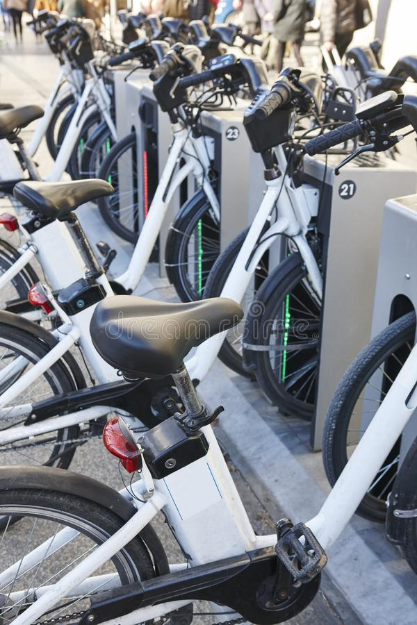 Bicicletas urbanas de carregamento da bateria elétrica na cidade Mobilidade sustentável fotos de stock royalty free