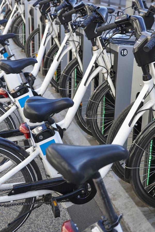 Bicicletas urbanas de carregamento da bateria elétrica na cidade Mobilidade sustentável fotos de stock